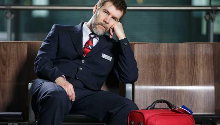 rhod gillbert sat on bench in smart suit