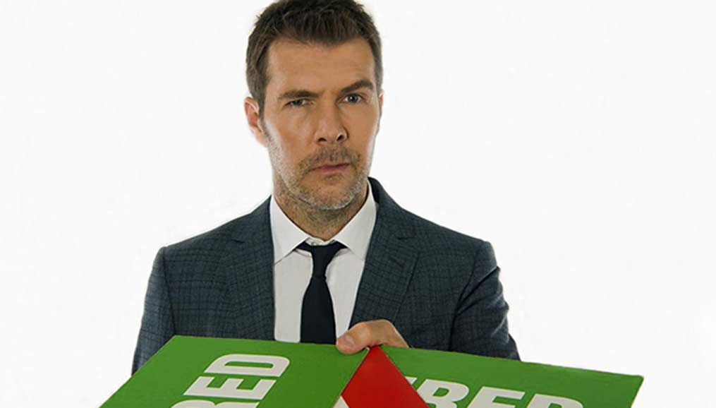 Rhod Gilbert holding 'hired' and 'fired!' cards in front of him
