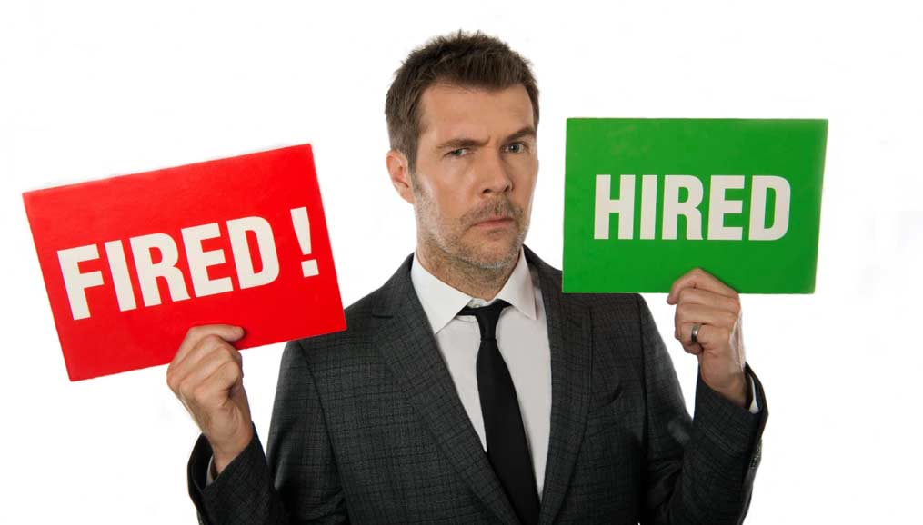 Rhod Gilbert holding 'hired' and 'fired!' cards